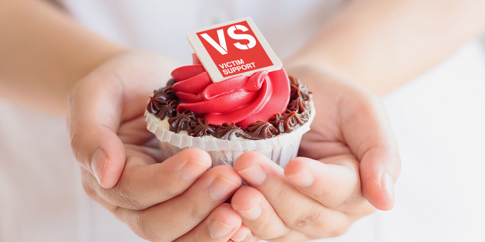 Hands holding a cupcake with a VS logo on top