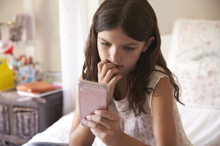 Young girl looking worried at her phone.