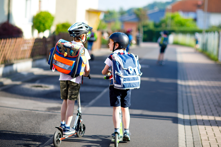 Two school boys riding scooters