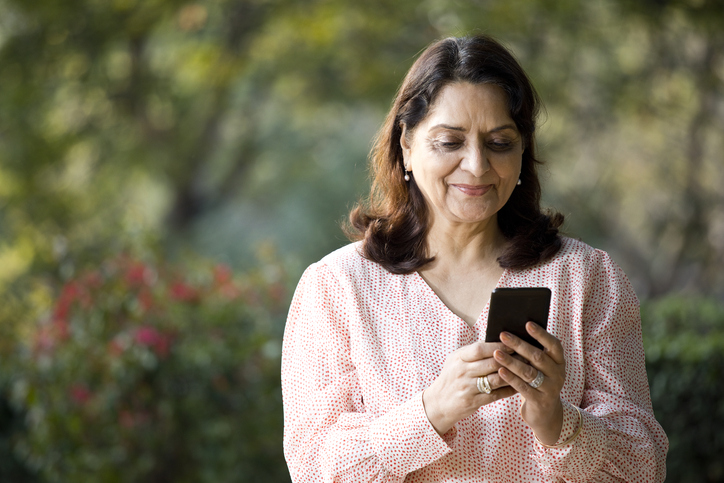 Older woman smiles at phone